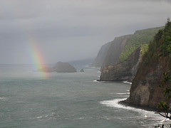 Rainbow curls over the black sand beach of the Pololu Valley on the Big Island of Hawaii